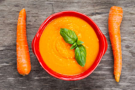 slurp: Carrot cream soup with basil on wooden table