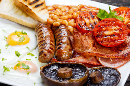 english food: Full English breakfast with bacon, sausage, fried egg, baked beans and mushrooms.
