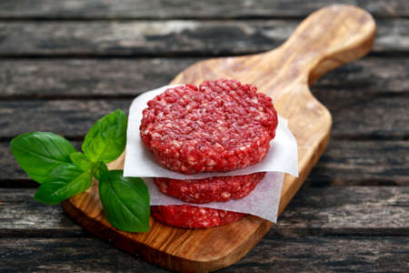 caked: Home HandMade Minced Beef burgers on cutting board. old wooden table.