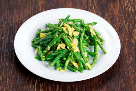 flaked: Green beans roasts garlic and flaked almond. Stock Photo