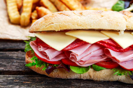 hum: Sandwich with lettuce, slices of fresh tomatoes, salami, hum and cheese. Stock Photo