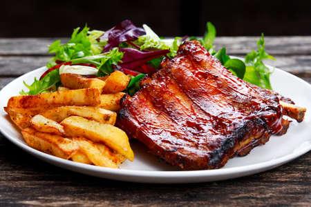 Asado de costilla de cerdo, patata frita en un plato blanco con verduras