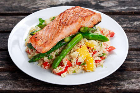 salsa: Pan fried salmon with tender asparagus and courgette served on couscous mixed with sweet tomato, yellow pepper salsa Stock Photo
