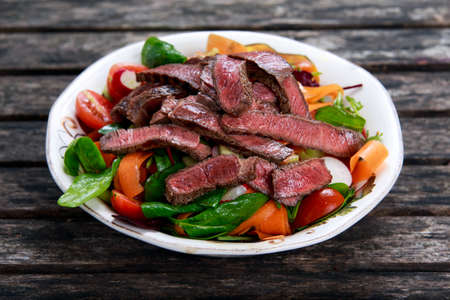 Spicy Beef Slices Meat Salad with Carrots, Tomatoes, Cucumber, Parsley, Radish and Salad leaves Spinach, rocket, red ruby chard on old wooden table Banco de Imagens