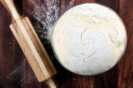 harina: Recién preparada la masa sobre una tabla de madera. Rodillo y la harina.
