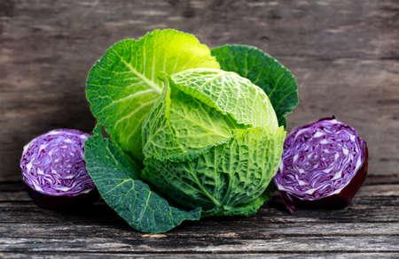 cabbage: Col verde fresca y una rebanada de col roja en tabla de madera