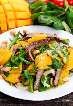 roast meat: Fresh Tasty Mango, beef salad with vegetables and nuts