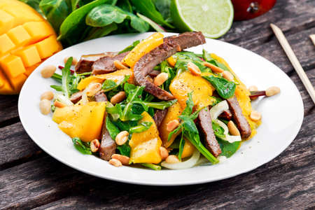 roast meat: Fresh Tasty Mango, beef salad with vegetables and nuts. on wooden table.