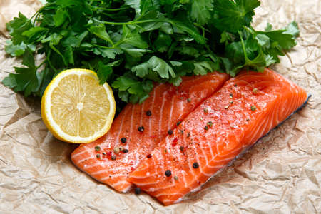 rosmarin: Raw Salmon fish fillet with fresh herbs on crumpled paper. Stock Photo