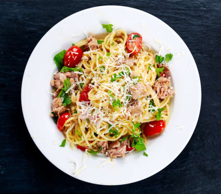 Italian Tuna Pasta spaghetti with tomato, chili, Parmesan cheese and wild rocket lives. on old blue stone background.