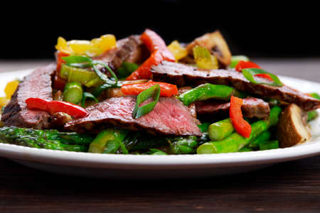 Stir-fry with beef and vegetables. Made with flank steak, peppers, onions and bok choy, stir fried in an Asian wok. Stock Photo