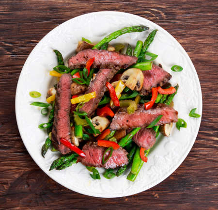 fry: Grilled steak with stir-fried vegetables on plate