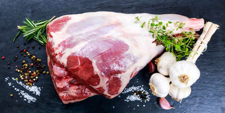 Raw lamb leg on blue stone background with herbs. Stok Fotoğraf