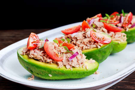 Avocado boats stuffed with tuna, red onion and cherry tomatoes seasoned with thyme. Imagens - 56356274