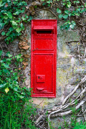 typically english: traditional old English red postbox mounted in stone wall surrounded by ivy Stock Photo
