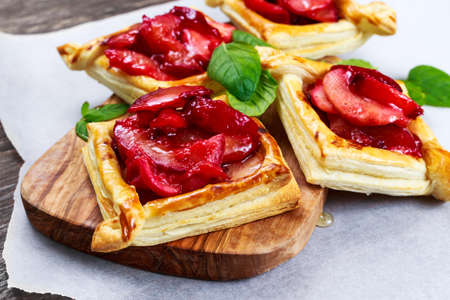 Puff pastry pies with plums, apples, mint and honey.