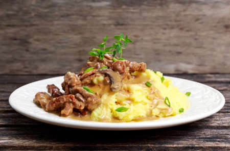 Beef Stroganoff with mashed potatoes on wooden table.