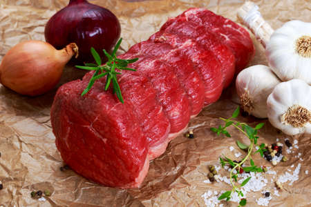 Fresh Raw beef tenderloin steak meat ready to cook with herbs.