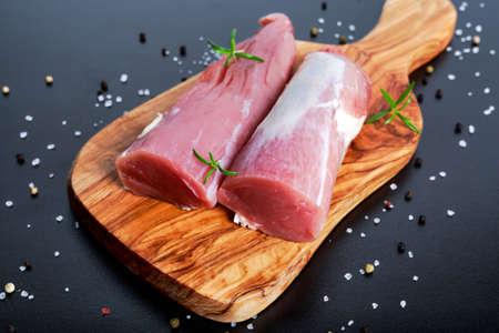 Fresh Raw pork tenderloin on wooden board .ready to cook.