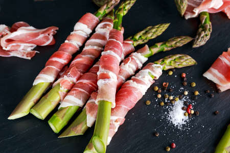 raw bacon: Fresh Organic raw Bacon Wrapped Asparagus on stone background.