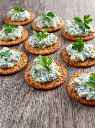 Bisquit cracker appetizers with cottage chees and parsley topping.