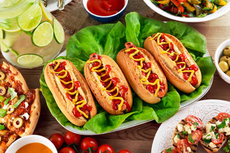 hot sauce: Hot Dogs with sausage, mustard and ketchup on lives salad.