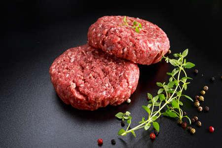 Home HandMade Raw Minced Beef steak burgers on black board. 스톡 콘텐츠