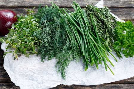 heathy diet: Fresh Green Vegetables. Onion, Dill, Rosemary, Parsley, Chives and thyme on old wooden table Stock Photo