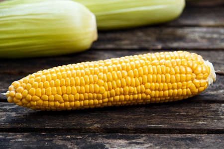 sweetcorn: close up Fresh Ripe Sweetcorn on old wooden table.