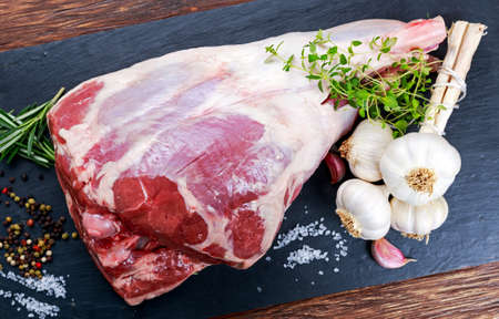 raw: Raw lamb leg on blue stone background with herbs. Stock Photo
