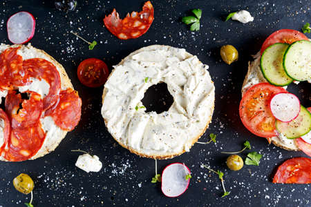 bublik: Delicious Bagel sandwiches with soft cheese, chorizo and vegetables.