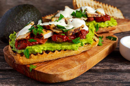Avocado Sandwich with sunshine dried tomatoes, roasted pork and sauce herbs.