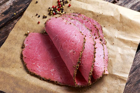 Peppered roast beef slices on paper with grains of coloured pepper
