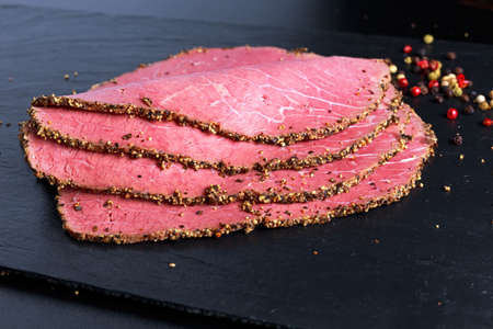 Peppered roast beef slices on stone board with grains of coloured pepper.
