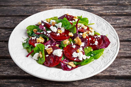 Healthy Beet Salad with fresh sweet baby spinach, kale lettuce, nuts, feta cheese on wooden table