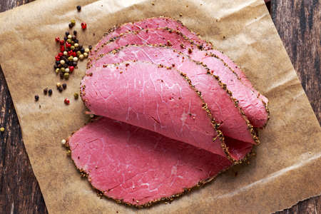Peppered roast beef pastrami slices on paper with grains of coloured pepper