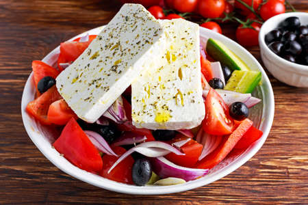 Greek salad with fresh sweet pepper, red onion, orange cherry tomatoes, cucumber, black olives and feta chees drizzled with extra virgin olive oil on wooden table. Stock Photo