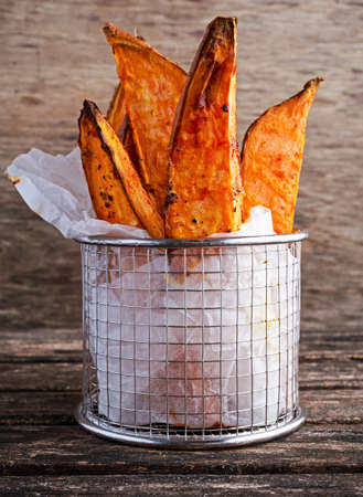 Freshly cooked sweet organic potato fries in paper wrap executed in a serving metal basket on old wooden table.