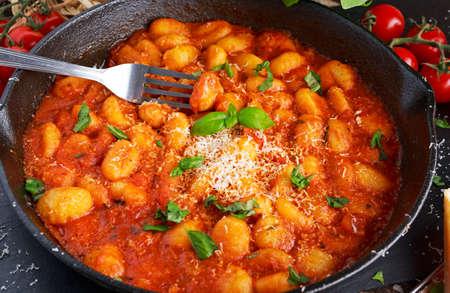 Homemade Italian Gnocchi with marinara sauce, cheese in iron pan. 스톡 콘텐츠