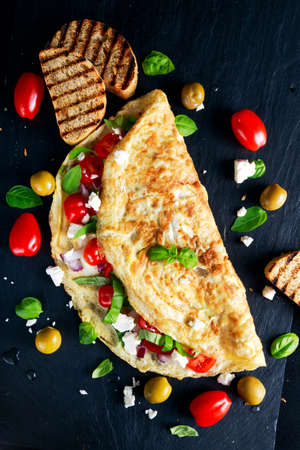Vegetables Omelette with tomatoes, basil, greek cheese, parmesan, olives, grilled toast on stone board 스톡 콘텐츠