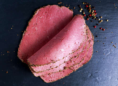 Peppered roast beef pastrami slices on paper with grains of coloured pepper Stock Photo - 60414772
