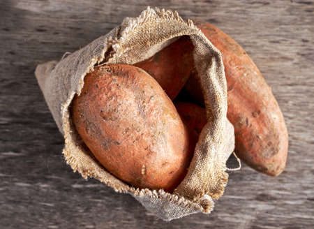 burlap bag: Freshly harvested organic sweet potatoes in a burlap bag on wooden table Stock Photo