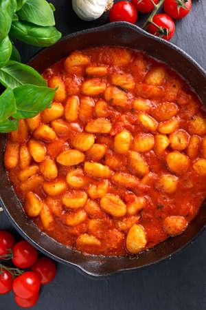 marinara sauce: Homemade Italian Gnocchi with marinara sauce in iron pan. Stock Photo