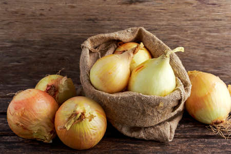 White freshly harvested onion in burlap bag on wooden old table. Banque d'images