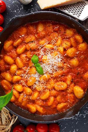 Homemade Italian Gnocchi with marinara sauce, cheese in iron pan. Stock Photo
