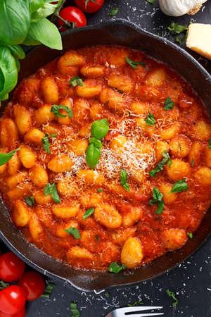 marinara sauce: Homemade Italian Gnocchi with marinara sauce, cheese in iron pan. Stock Photo