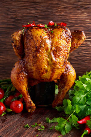 rotisserie chicken: Gourmet Roast Whole organic chicken on cider Can With Asparagus, glazed Cherry Tomatoes, Herb and Spices, Served on Top of a Wooden Table