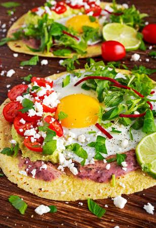 Huevos Rancheros Breakfast tostadas with avocado, feta cheese and vegetables