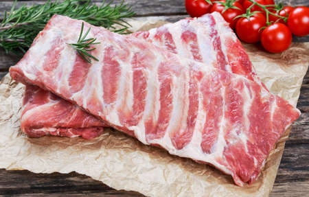 Raw Pork ribs with a rosemary and vegetables. on crumpled paper Stock Photo