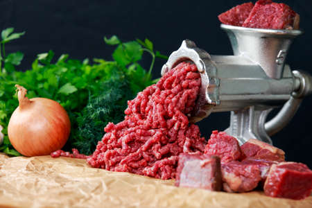 Mincer with fresh minced beef meat with vegetable.